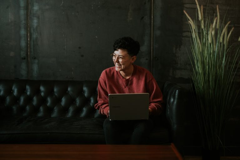 Photo of person with laptop smiling