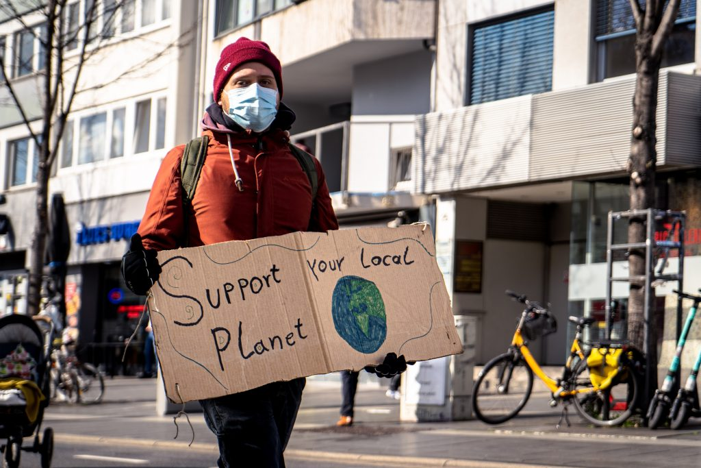 A young person with a sign supporting a message of environmental protection